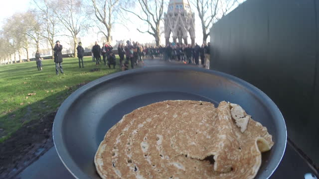 exterior gopro travelling shot of a frying pan being carried through crowds of onlookers in westminster in an annual pancake race between poilticians... - 四旬節点の映像素材/bロール