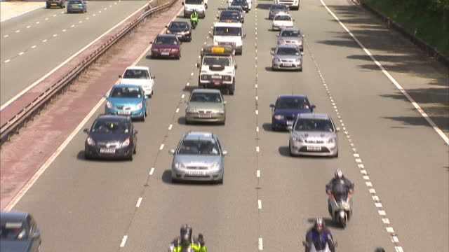 exterior high shot from bridge at convoy of cars, motorbikes & lorries driving slowly along the m56. a convoy of fuel protesters are attempting to... - 英チェシャー州点の映像素材/bロール