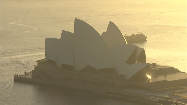 exterior high shot of the sydney opera house lit up by a golden early morning light>> on april 19 2014 in sydney australia - bennelong point stock videos and b-roll footage