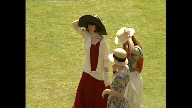 Exterior high shot of woman's hat blowing off head due to wind at garden party and shots of other women holding onto their hats on July 11 1991 at...
