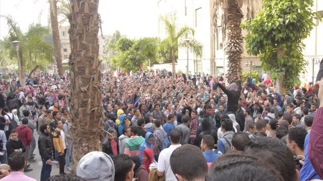 vídeos de stock, filmes e b-roll de exterior high shot thousands of protesters chanting at protest against acquittal and release of former president hosni mubarak on november 30 2014 in... - arab spring