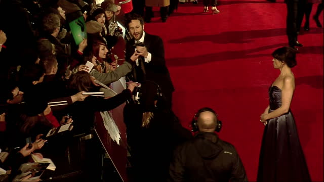 vídeos de stock e filmes b-roll de exterior high shots chris o'dowd poses with fans signs autographs on the red carpet at the bafta arrivals chris o'dowd on the bafta 2012 red carpet... - autografar