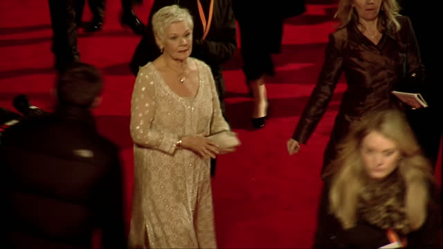 stockvideo's en b-roll-footage met exterior high shots dame judi dench walks the red carpet sings autographs for fans at the 2012 bafta awards dame judi dench bafta red carpet on... - signeren