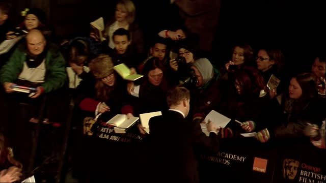 vídeos de stock e filmes b-roll de exterior high shots james corden walks the red carpet signing autographs for fans james corden on the bafta red carpet on february 12 2012 in london... - autografar