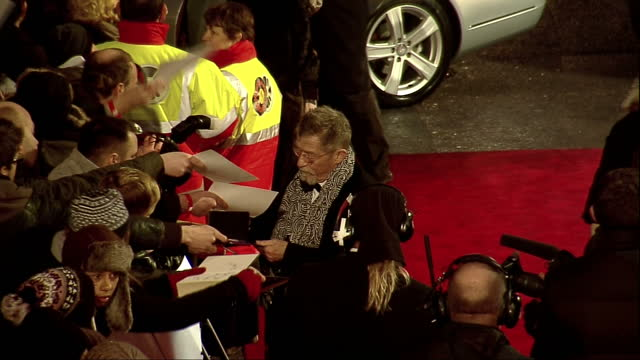 stockvideo's en b-roll-footage met exterior high shots john hurt walks on the red carpet at the bafta awards arrivals signing autographs for fans john hurt on the bafta red carpet on... - signeren