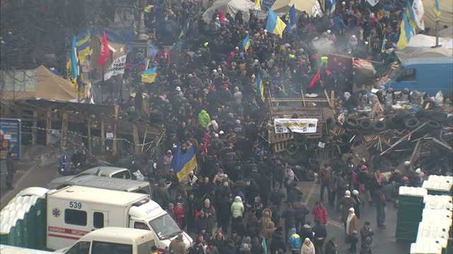 exterior high shots of crowds of pro-europe protesters in kiev's independence square, with many tents, ukrainian and european union flags. protesters... - キエフ市点の映像素材/bロール