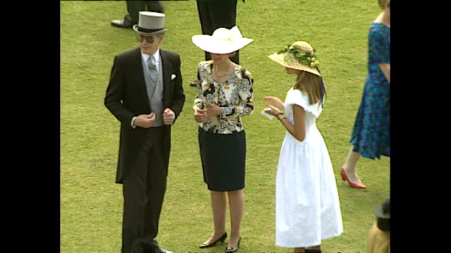 Exterior high shots of guests walking around Buckingham Palace Gardens during party on July 11 1991 at Buckingham Palace in London England
