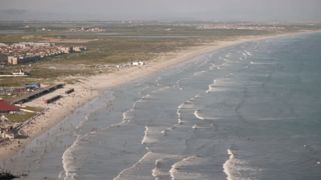 exterior high shots over cape town beach with waves sweeping in and people swimming in surf on 24 september 2019 in cape town south africa - indian ocean stock videos & royalty-free footage