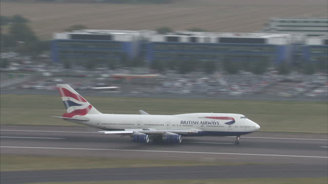 exterior high shots overlooking heathrow airport and surrounding fields on an overcast day, including shots of british airways planes landing.>> on... - surrounding stock videos & royalty-free footage