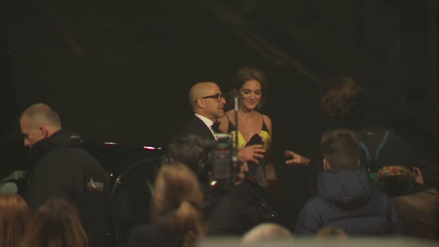 Exterior high wide shot Stanley Tucci actor arrives with wife Felicity Blunt and they pose on the red carpet together at the BAFTA Awards at the...