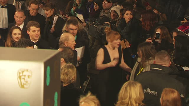Exterior high wide shots of Bryce Dallas Howard actress on red carpet amongst sea of heads signing autographs at the BAFTA Awards at the Royal Albert...