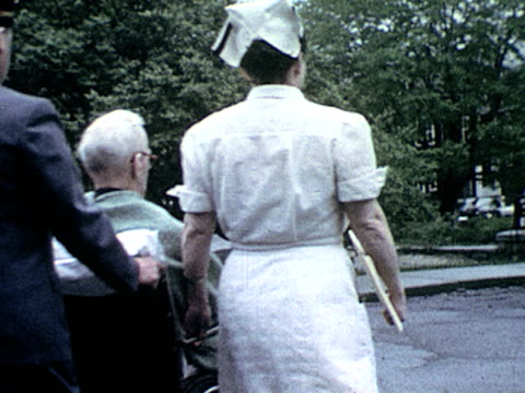 / exterior hospital nurse with folder accompanies man pushing older gentleman in wheelchair as they exit hospital on january 01 1955 - leaving hospital stock videos & royalty-free footage