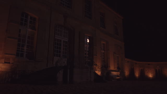 exterior lights illumine the walls of the chateau de villette in condecourt, france; a light goes on inside. - stately home stock videos & royalty-free footage