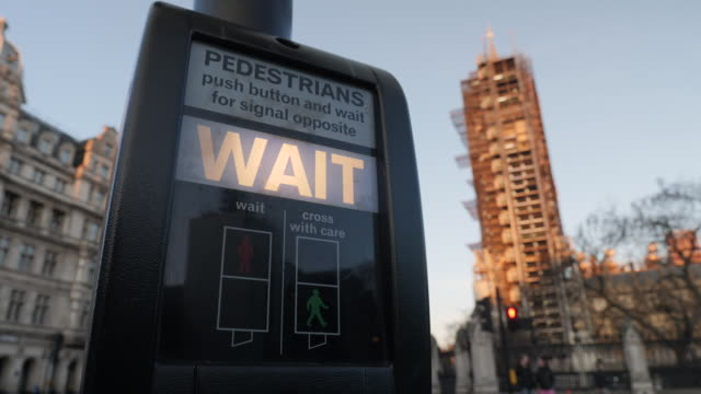 exterior locked off shot of a pedestrian traffic lights button highlighted wait on the 25th march 2020 in london england - road signal stock videos & royalty-free footage