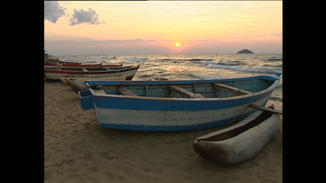Exterior locked off shot of a wooden boat on the beach with Lake Malawi and the sunset in the background on August 12 2002 in Malawi