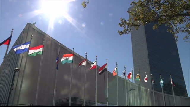 stockvideo's en b-roll-footage met exterior locked off shot un building with the nations flags fluttering in the breeze united nations building locked off exterior on september 25 2012... - united nations