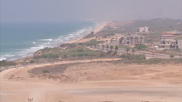 exterior locked off wide shot ashkelon skyline with waves crashing into shore - ashkelon stock videos and b-roll footage