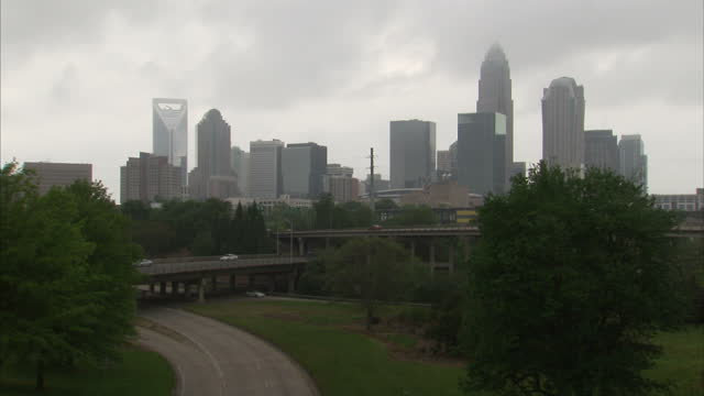 Exterior long lockedoff shot of Raleigh NC's skyline with clouds passing skyscrapers and traffic on highway useful for timelapse sequences on April...