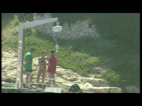 exterior long shots: princess diana standing on beach outside private villa in st tropez. she wears leopardskin print swimsuit. princess diana on st... - anno 1997 video stock e b–roll