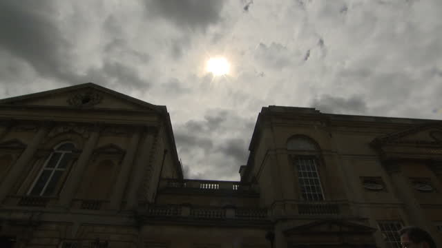 exterior low shot of bath abbey cathedral arty view of cloudy sky with sun peeking through clouds obscured by mist with dark cathedral building in... - somerset england stock videos & royalty-free footage