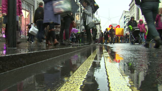 Exterior low shot of muddy puddle outside Top Shop in gutter of Oxford Street busy with Christmas shoppers walking in rain carrying umbrellas and...