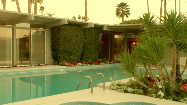 WS TS exterior mid-century modern country club home with floor to ceiling glass windows looking out across swimming pool