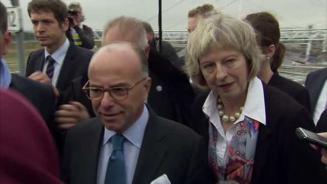 exterior mid-shots of theresa may mp and bernard cazeneuve walking through crowd of journalists and get on bus after meeting about co-operation... - bernard cazeneuve stock videos & royalty-free footage