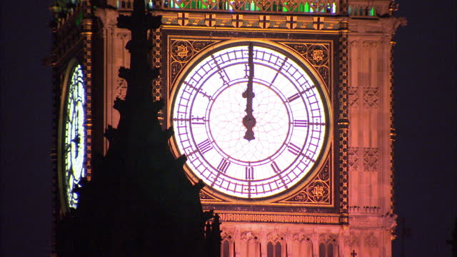 Exterior night shot close up of Big Ben striking midnight on New Year's Eve into New Year's Day and fireworks come out of Big Ben's tower fireworks...
