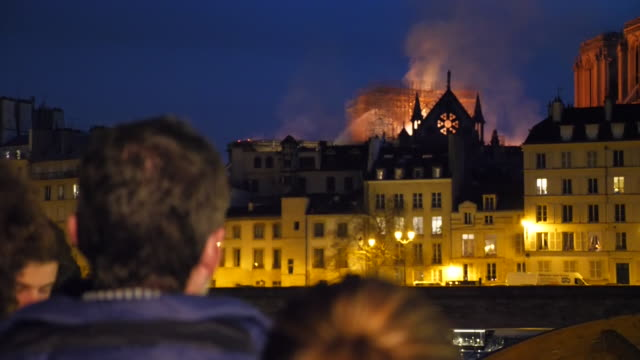 exterior night shot of notre dame de paris cathedral on fire while people are looking at it from across the river on 15th april 2019 in paris, france. - テロリズム点の映像素材/bロール