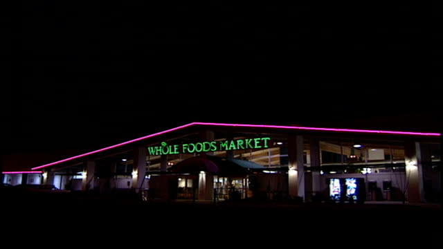 exterior night shot whole foods market with neon sign and lights in san antonio tx - whole foods market stock videos and b-roll footage