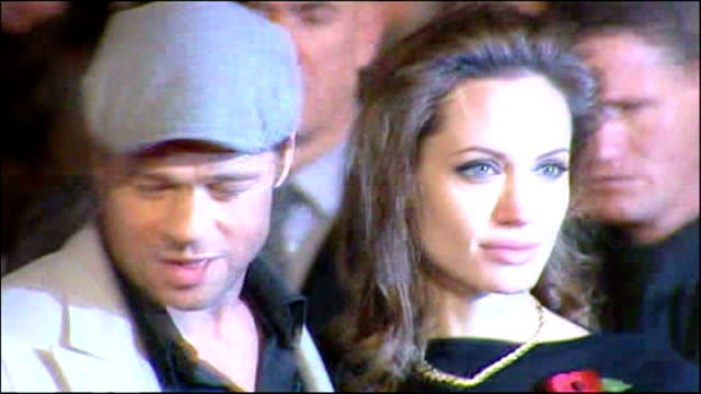 Exterior night shots Brad Pitt and Angelina Jolie posing on red carpet at Beowulf film premiere