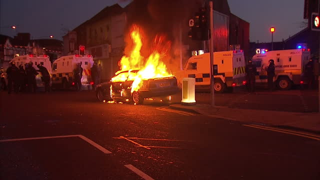 exterior night shots car burns on the streets of belfast exterior night shots psni vehicles move in towards the burning vehicle car burns on during... - belfast stock videos & royalty-free footage
