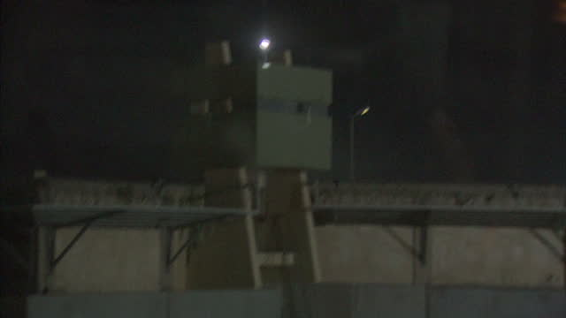 Exterior night shots driving past high walls watch towers of Gaddafi family compound Exterior night shots proGaddafi supporters waving flags singing...