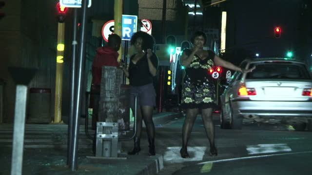 vídeos de stock, filmes e b-roll de exterior night shots female prostitutes in the street speaking to a man waving at cars to stop prostitutes working in johannesburg at night on june... - prostituta