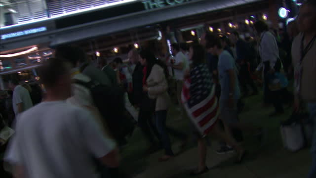 exterior night shots large crowds of people walking in the olympic park after leaving the olympic stadium in the aftermath of the london 2012 closing... - オリンピックスタジアム点の映像素材/bロール