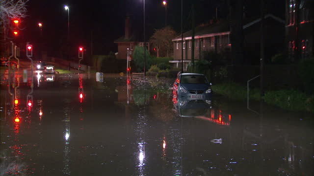 Exterior night shots of a flooded street in Whalley Lancashire with partly submerged cars and houses on December 27 2015 in Whalley United Kingdom