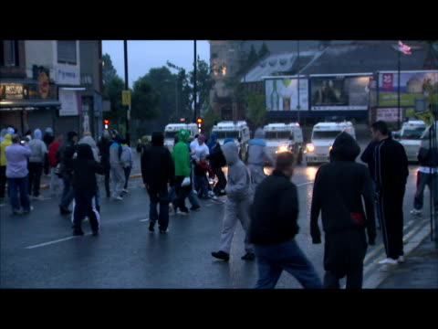 exterior night shots of a line of hooded rioters throwing stones rocks towards line of armoured police vehicles following another night of... - belfast stock videos & royalty-free footage