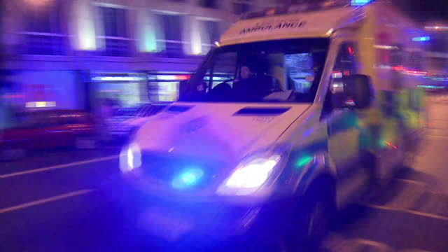exterior night shots of ambulances driving away from the scene of the terror attack near london bridge, people evacuating the area and emergency... - violence stock videos & royalty-free footage