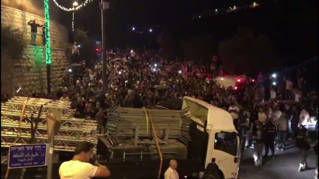 Exterior night shots of angry crowds of Palestinian protesters outside the Al Aqsa Mosque shouting on 27 July 2017 in Jerusalem Israel