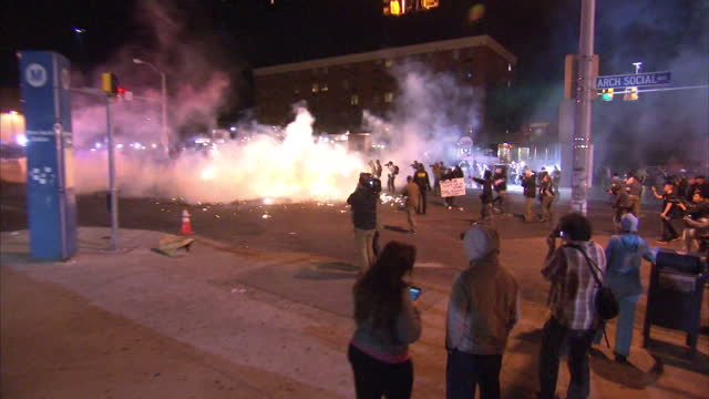 exterior night shots of baltimore police advancing with riot shields towards protesters then missiles being thrown including smoke grenades on april... - baltimore maryland bildbanksvideor och videomaterial från bakom kulisserna