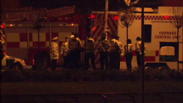 exterior night shots of emergency services at the scene of a helicopter crash at the clutha pub in glasgow and part of the wreckage of the crashed... - ヘリコプター事故点の映像素材/bロール