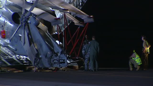 exterior night shots of helicopter being taken off cargo plane to be used in search for missing mh370 with crew unloading chopper and then... - malaysia stock-videos und b-roll-filmmaterial