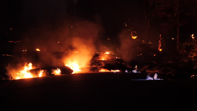 exterior night shots of lava burning and engulfing roads and forests after hawaii's kilauea volcano erupted on 24 may 2018 in kilauea, hawaii. - hawaii islands stock videos & royalty-free footage