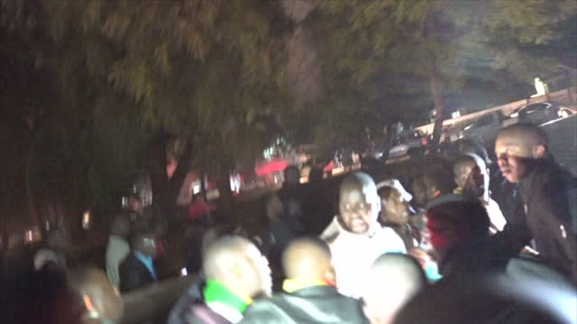 exterior night shots of pastor evan mawarire walking among cheering crowd holding the holy bible one his supporters carrying a cross in front after... - pastor stock videos & royalty-free footage