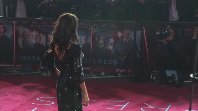 Exterior night shots of Penelope Cruz posing on the red carpet and signing autographs at the world premiere of Murder on the Orient Express on...