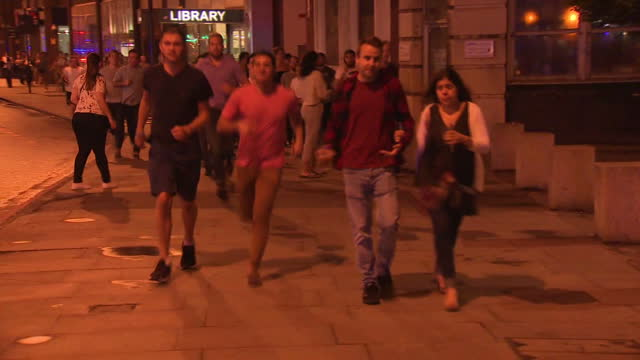 exterior night shots of people being evacuated from the scene of the terror attack near london bridge, including shots of a man walking with a pint... - terrorism stock videos & royalty-free footage