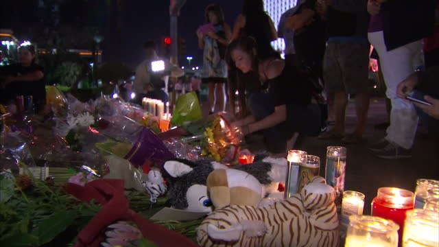 exterior night shots of people lighting candles and looking at tributes to the victims of the las vegas mass shooting attack on october 04 2017 in... - mandalay bay resort and casino stock videos & royalty-free footage