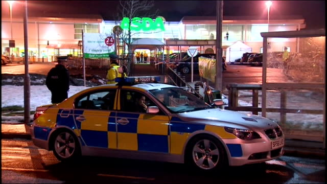 exterior night shots of police activity in asda car park in robroyston after kevin carroll was shot dead there police gathered at entrance to car... - gang stock videos and b-roll footage