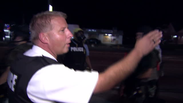 Exterior night shots of police arresting two men and a police officer telling onlookers and media to move away to another area>> on August 19 2014 in...