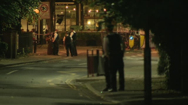 vídeos de stock e filmes b-roll de exterior night shots of police officers on guard and stood by police cordon tape at the crime scene where a man was shot in the face including shots... - peckham